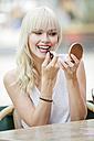 Portrait of blond woman sitting at sidewalk cafe applying lipstick - GDF001104