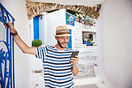 Greece, Amorgos island, young man using a smartphone - GEMF000952