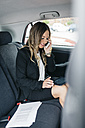 Businesswoman using cell phone and digital tablet in car - DAPF000200