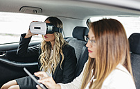 Two businesswomen with VR glasses and digital tablet in car - DAPF000209