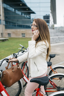 Businesswoman with bicycle on cell phone - DAPF000215
