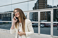 Happy businesswoman on cell phone in front of office building - DAPF000221