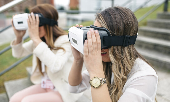 Two women having fun with VR glasses sitting outdoors - DAPF000239