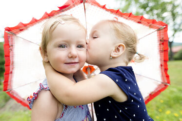 Little girl kissing her sister under an umbrella - HAPF000688