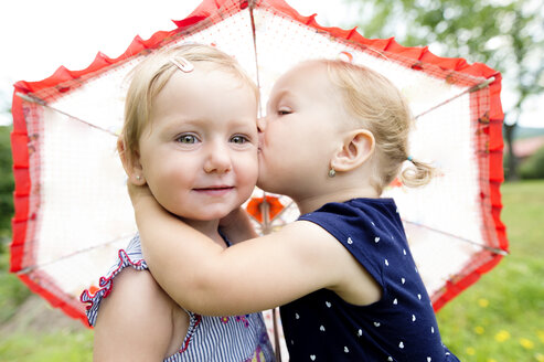 Little girl kissing her sister under an umbrella - HAPF000688