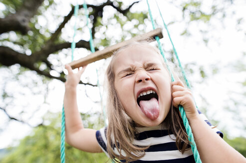 Little girl on a swing sticking out tongue - HAPF000691