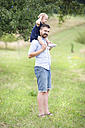 Happy father carrying little daughter on shoulders in nature - HAPF000694