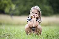 Little girl crouching on a meadow - HAPF000697