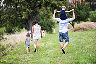 Back view of family with two children walking on a meadow - HAPF000700