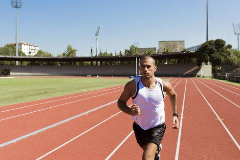 Young sportsman running on tartan track - FMOF000067