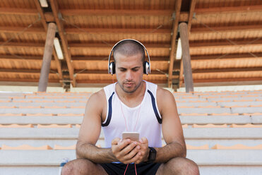Young sportsman with headphones and smartphone - FMOF000070