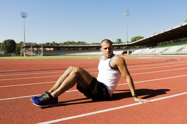 Young sportsman sitting on running track - FMOF000085