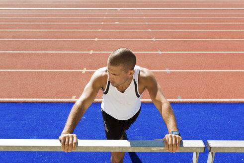 Young sportsman stretching, railing - FMOF000088