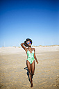 Young woman walking on the beach - KIJF000642