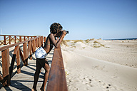 Young woman taking photos on the beach - KIJF000651