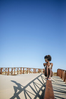 Young woman sitting on the railing of a walkway on the beach - KIJF000654