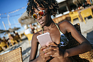 Young woman using a smartphone in a beach bar - KIJF000663
