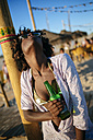 Young woman on the beach relaxing with a bottle of beer - KIJF000675