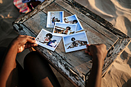 Woman's hands with instant photos on a wooden table on the beach - KIJF000681