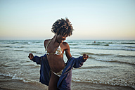 Happy young woman dancing at the seafront at sunset - KIJF000690
