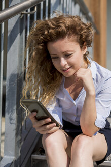 Businesswoman sitting on stairs using cell phone - MAUF000692
