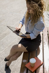 Businesswoman sitting on bench using digital tablet - MAUF000701