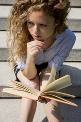 Woman sitting on stairs reading a book - MAUF000710