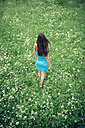 A young woman in a blue dress walk through a summer meadow - MW000108
