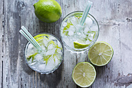 Glasses of infused water with lime and ice cubes - JUNF000546