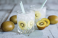 Glasses of infused water with kiwi and ice cubes - JUNF000549