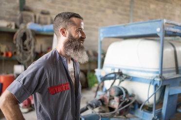 Smiling man in workshop looking away - JASF001055