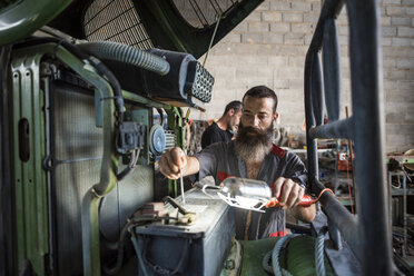 Mechanic repairing tractor - JASF001058