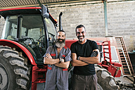 Portrait of two confident mechanics at tractor - JASF001064