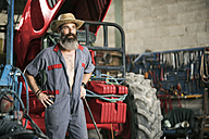 Portrait of confident mechanic with hat at tractor - JASF001079