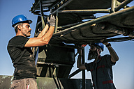 Two men working at conveyer belt outdoors - JASF001088