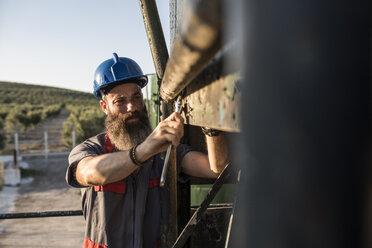 Mechanic working at machine outdoors - JASF001091