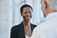 Smiling businesswoman looking at businessman - RORF000218