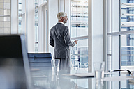 Businessman looking out of the window - RORF000227