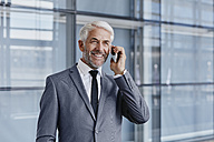 Smiling businessman on cell phone - RORF000236