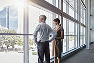 Two business people looking out of a big window - RORF000248