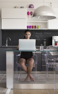 Young woman sitting at table in the kitchen working with laptop - MOMF000017