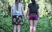 Back view of two fashionable female friends standing hand in hand, partial view - MOMF000026