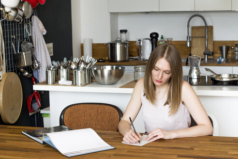 Woman sitting at table in her kitchen writing down something - LMF000581