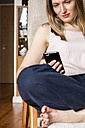 Woman sitting on chair at home looking at cell phone - LMF000587