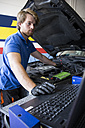 Mechanic fixing a car engine while using a computer in his workshop - ABZF000939