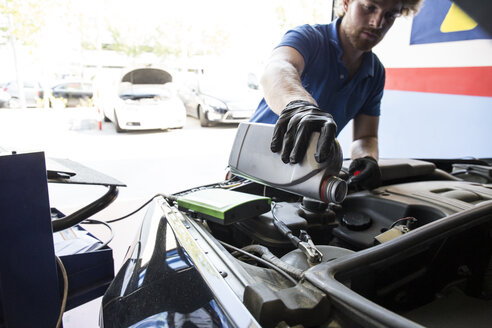 Mechanic refilling oil in a car - ABZF000948