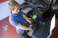 Mechanic using a computer while fixing a car - ABZF000951