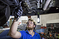 Mechanic fixing suspended car in his workshop - ABZF000954