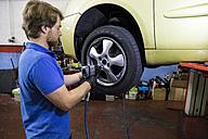 Mechanic fixing a car wheel in a workshop - ABZF000960