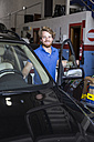 Smiling mechanic with a car in his workshop - ABZF000966